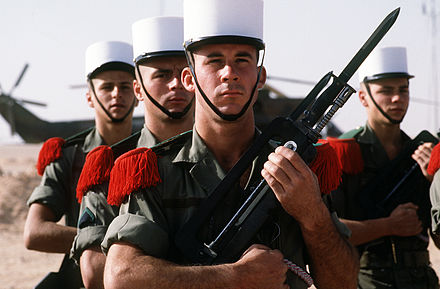 A Legion honour guard of the 2nd Foreign Infantry Regiment stands at attention as they await the arrival of Norman Schwarzkopf, Jr. and Lt. Gen. Khalid bin Sultan bin Abdul Aziz, commander of Joint Forces in Saudi Arabia, during Operation Desert Shield.[2] - French Foreign Legion