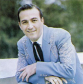 A dark-haired man wearing a blue jacket and black tie, smiling broadly