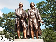 Photograph of a statue of Goethe and Schiller standing side by side, each looking forward. There are trees and blue sky visible behind the statue. The two figures are of nearly the same height. Goethe appears middle-aged; Schiller is noticeably younger. They are dressed in nineteenth century clothing. Goethe is wearing a knee-length formal coat, and Schiller is wearing a calf-length coat. Both men wear breeches. Goethe's left hand rests lightly on Schiller's shoulder; his right hand holds a laurel wreath near his waist. Schiller's right hand is nearly touching the wreath, which may suggest that Goethe is passing the wreath to Schiller. Schiller's left hand extends loosely below his waist, and grasps a rolled sheet of paper.