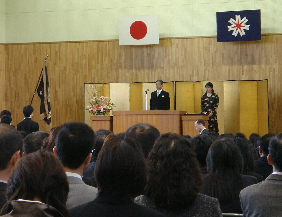 A group of people facing a man and woman on a stage. Two flags are above the stage.