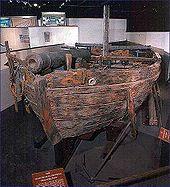 El barco se muestra en una instalación de museo, montado sobre un marco de madera.  La carpintería del barco se ha decolorado, y el barco tiene un mástil corto, un solo cañón mirando hacia adelante cerca de la proa y dos cañones mirando a babor y estribor respectivamente cerca de la popa.