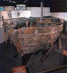 The ship is shown in a museum installation, mounted on a wooden framework. The ship's woodwork has been discolored, and the ship sports a short mast, a single cannon facing forward near the bow, and two cannons facing port and starboard respectively near the stern.