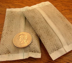 Hand warmer - A pair of air-activated disposable hand warmers, US quarter for scale.