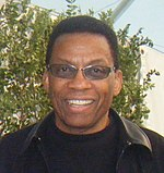 An African American male in his late sixties is wearing sunglasses, a black jacket, and a black t-shirt.