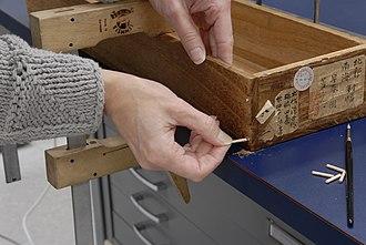 Conservation technician - A conservation technician repairing a Japanese scroll box.
