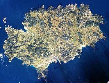 Satellite photo (2013) showing terrain and towns as lighter areas: Ibiza Town (bottom central bay), Sant Antoni (upper left bay) and Santa Eularia (lower right). Airport runways cross the southern point. Ibiza ISS035-E-007431.jpg