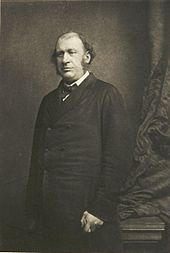 A black-and-white photograph of James Fitzjames Stephen, a balding man with sideburns. He stands looking to the left of the camera near a curtain. He is holding a cane in his left hand.