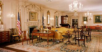 Diplomatic Reception Rooms, U.S. Department of State - John Quincy Adams State Drawing Room. The 1783 Treaty of Paris, ending the Revolutionary War, was signed on the desk in the foreground. The unfinished painting over the mantel depicts Benjamin Franklin and John Adams signing that treaty.