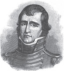A man with dark hair wearing a high-collared, black military jacket