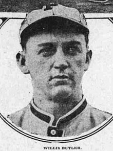 "A man in a light-colored baseball uniform and a cap with a ""P"" on the front looks to the right."
