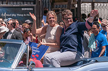 Two women sitting on the top of the back seat of an open-top automobile waving to a crowd.