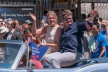 Dos mujeres sentadas en la parte superior del asiento trasero de un automóvil descapotable saludando a una multitud.