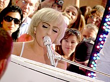 A blond woman with short cropped hair, singing to a microphone, in front of a piano. Faces of the crowd can be seen behind her.