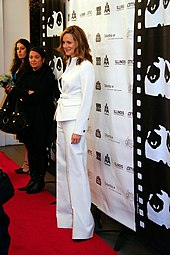 a dirty blonde woman in a white pant suit stands on a red carpet with two women in the background