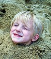 Little girl buried up to her neck in sand.jpg