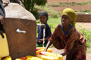 Water scarcity in Africa - Local girls from Babile fill yellow water jugs at the area's main water source, May 26, 2012