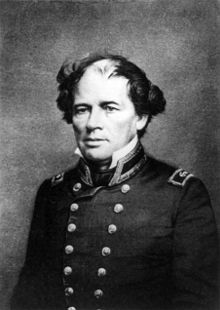 Photograph of a man, seated, with balded head, wild hair, in double-breasted naval uniform