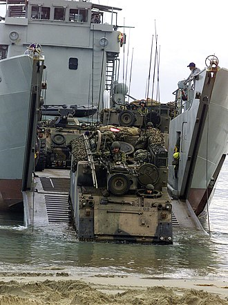 Balikpapan-class landing craft heavy - M-113 armoured personnel carriers disembarking on a beach from a Balikpapan-class landing craft