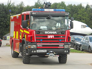 Fire engine red - A red fire appliance with half-Battenburg side markings at Manchester Airport, UK