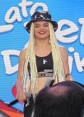 Smiling Margaret performing on-stage. She is wearing a crop top and a bucket hat.