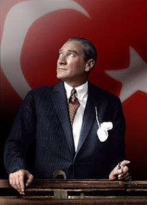 Mustafa Kemal Ataturk looking through a train window over Turkish flag.jpg