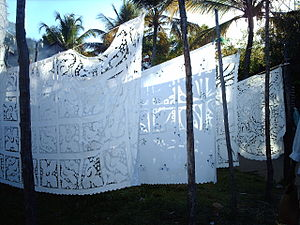 embroidered tablecloths hang on lines from palm trees