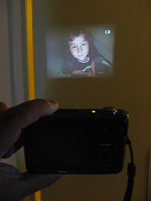 Handheld projector - The Nikon Coolpix S1000pj compact camera projecting an image using its built-in projector.