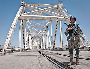 Afghanistan–Uzbekistan Friendship Bridge - An Afghan Border Police officer standing on the Afghan side of the Afghanistan–Uzbekistan Friendship Bridge.
