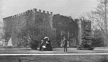 An old black-and white photograph showing a three-storey battlemented house, in front of which is a standing male and two sitting females
