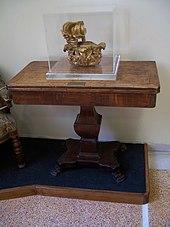 En ødelagt krone under en glassramme, plassert på et trebord.