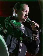 An man singing to a microphone and wearing a charro suit.