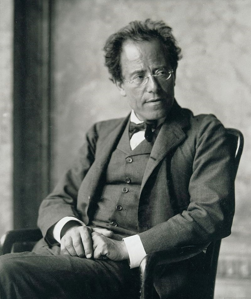 Middle-aged man, seated, facing towards the left but head turned towards the right. He has a high forehead, rimless glasses and is wearing a dark, crumpled suit