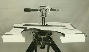 Plane table - A plane table cutaway.   This shows a plane table with part of the surface of the table cut away to show the mounting on the tripod.  The mount allows the table to be levelled.  On the table, the alidade with telescopic sight is seen