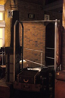 "Photograph of a hotel-style metal-framed luggage trolley surrounded by old-style suitcases. In the background is what appears to be a solid brick wall. with platform number sign ""10"" on the left, and ""9"" on the right. The trolley contains a human-sized semi-transparent mirror that combines the foreground and background."