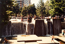 Columns with water flowing over the top, falling into a pool with square platforms. People are sitting and standing on the columns as well as the square platforms. In the background are trees and other buildings.