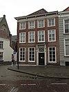 foto van Huis op de hoek van de kerkstraat, met geelgeverfde lijstgevel, schilddak, kroonlijst op consoles, lage zolderverdieping