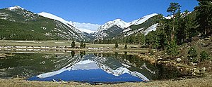 Horseshoe Park - Sundance Mountain (12,466 feet) on left, Mount Chaplin (12,454 and Mount Chiquita (13,069 feet) reflect in one of the Sheep Lakes in Horseshoe Park shortly after the ice had melted in the spring. Courtesy of Rocky Mountain National Park.