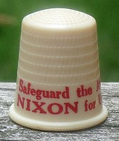 "Beige thimble with red lettering, the visible part of which says ""Safeguard the A..."" and ""NIXON for U..."