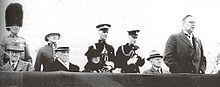 News photo of Reid, making a speech, outdoors in a reviewing stand. A number of other dignatories are seated in the stand, and behind them stand four members of the armed services, in dress uniform.