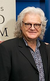 A man with long grey hair wearing glasses, a dark jacket and a blue and white shirt