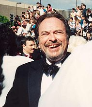 Rip Torn, a caucasian male in his early-60s with dark hair, wears a black suit and white shirt with a black bow-tie. He laughs and smiles.