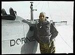 Roald Amundsen i selskinnspels foran et av Dornier Wal-flyene (11963186344).jpg