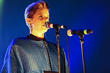 Robyn singing on a dark stage, in front of two microphones