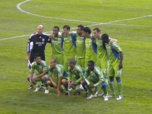 Eleven soccer players wearing green jerseys and green shorts posing in two rows on a grass field.