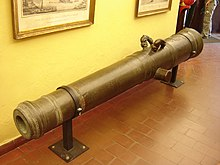 A metal cannon barrel mounted upon two brackets screwed into a brown tiled floor. The cannon barrel is mounted in front of a pale yellow wall supporting two picture frames.