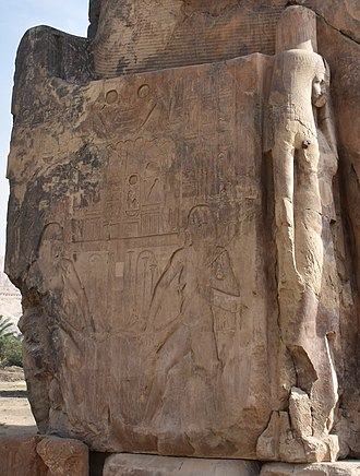Colossi of Memnon - Side panel detail showing two flanked relief images of the deity Hapi and, to the right, a sculpture of the royal wife Tiy