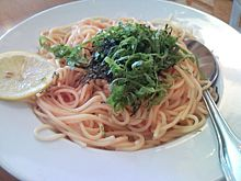 A white bowl of spaghetti in red sauce, ganished with minced nori and julienned shiso leaves
