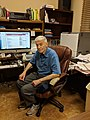 Stephen Barrett seated at desk 1.jpg