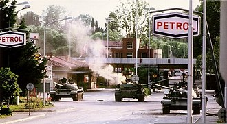 Slovenian Territorial Defense Units counterattacking the Yugoslav National Army tank who entered Slovenia during the Ten-Day War, 1991 Teritorialci so z armbrustom zadeli tank v kriziscu pred MMP Rozna Dolina..jpg