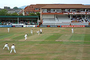 grass covered pitch with players in white clothes.